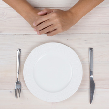 Hands resting in front of a plate and utensils on a table